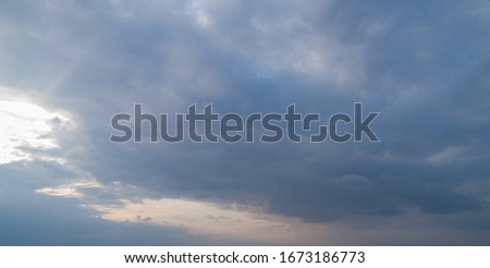 Dark cloudy sky with red reflections at sunset #1673186773