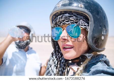 Woman with motor bike helmet and sun glasses in desert ride.Headshot selfie Portrait of pretty Woman biker with man drinking water in Sahara safari #1673188276