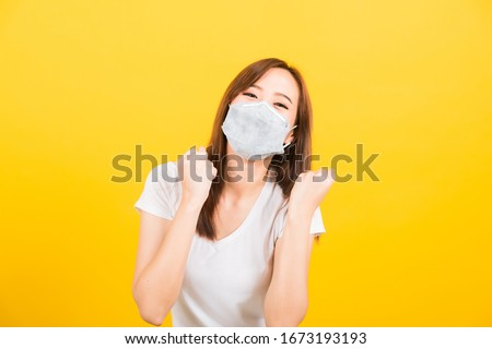 Portrait Asian beautiful happy young woman wearing face mask protects filter dust pm2.5, virus and air pollution her raise hands glad excited cheerful after recover from illness on yellow background #1673193193