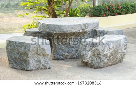 Table and chairs made of marble rock stone at outdoor. Vintage style #1673208316