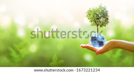 Card for World Earth Day or Arbor Day. Blue glass globe ball and tree in human hand on blurred green background. Saving environment, save, protect clean planet and ecology, sustainable lifestyle. #1673221234