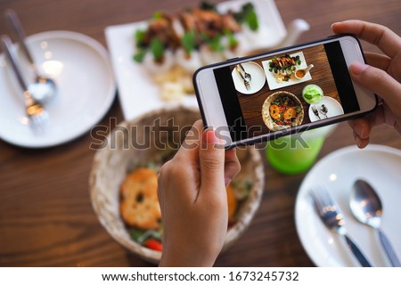 The hand of a woman take pictures of food made by herself. Food sellers take photo with a smartphone to post on the online food ordering website.