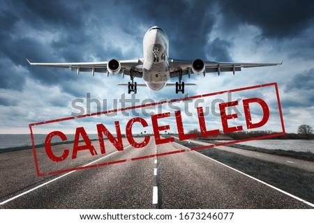 Canceled flights in Europe and USA airports. Travel vacations cancelled because of pandemic of coronavirus. Flying passenger airplane and runway. Flight cancellation. Aircraft with text. Covid-19 #1673246077