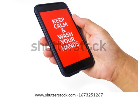 "A hand holding a mobile phone with the words ""Keep Calm and Wash Your Hands"" on the screen. white backgorund"