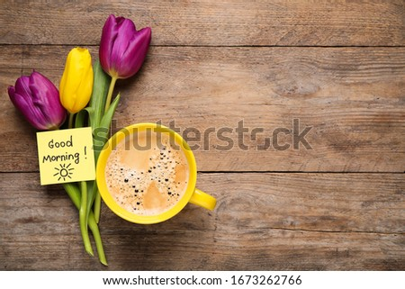 Delicious coffee, flowers and card with GOOD MORNING wish on wooden table, flat lay. Space for text