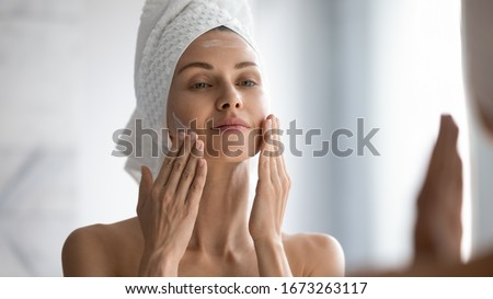 Closeup head shot pleasant beautiful woman applying moisturizing creme on face after shower. Smiling young pretty lady wrapped in towel smoothing perfecting skin, daily morning routine concept. #1673263117