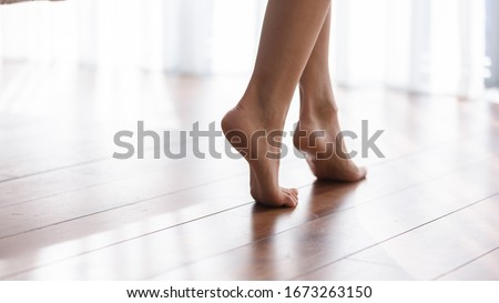 Close up focus on young female feet walking barefoot on clean wooden floor at home. Cropped image millennial woman girl standing on warm floor without slippers indoors, underfloor heating concept. #1673263150