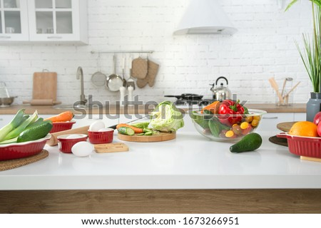 Modern stylish kitchen interior with vegetables and fruits on the table . Bright white kitchen with household items . The concept of a healthy lifestyle. #1673266951