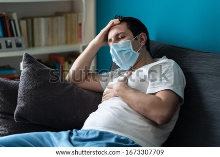 A sick caucasian Man wearing face mask feeling sick headache and cough because of Coronavirus Covid-19 on the sofa in quarantine Royalty-Free Stock Photo #1673307709