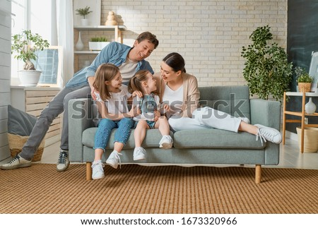 Happy family! Two children daughters with mother and father. Mum, dad and girls laughing and hugging.                                 #1673320966
