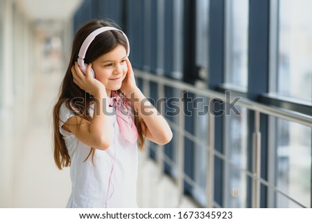 stylish girl listening to music pink headphones #1673345923