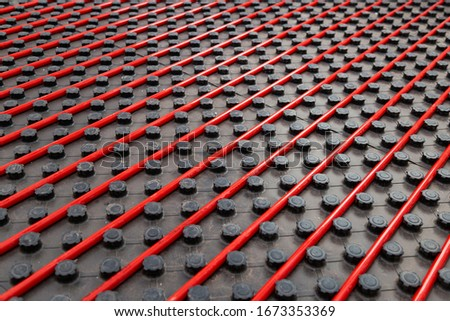 Radiant underfloor heating installation with red flexible tubing mounted on black insulation boards Royalty-Free Stock Photo #1673353369
