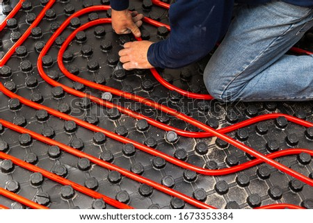 Worker who install tubes of radiant underfloor heating installation  Royalty-Free Stock Photo #1673353384