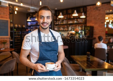 Young cheerful waiter in white t-shirt and blue apron holding cup of cappuccino on saucer while looking at you #1673354023