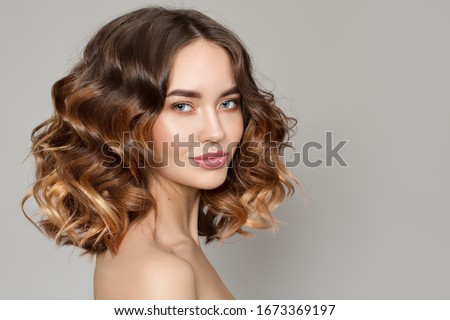 Portrait of a woman with curly hair. Haircut. Shine and hair care Royalty-Free Stock Photo #1673369197