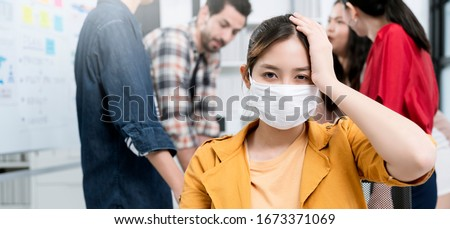 sick asian worker female wear mask with covid19 corona flu disease infection sit and hand touch head in meeting room with background of colleague office friend discussion office background  #1673371069