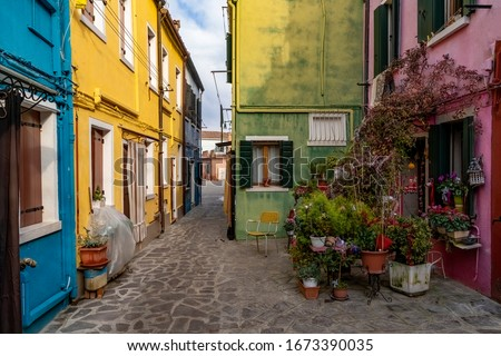 Burano, Italy - 3 January 2020 - Colorful houses and boat by the water canal at the island Burano  #1673390035