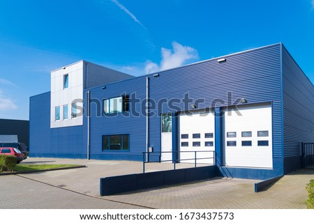 exterior of a modern warehouse with a small office unit Royalty-Free Stock Photo #1673437573