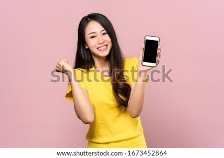 Portrait photo of young beautiful Asian woman feeling happy or surprise shock and holding smart phone with black empty screen on pink background can use for advertising or product presenting concept. #1673452864