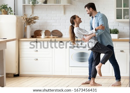 Happy loving young couple dancing romantic dance on date in modern kitchen, smiling husband and wife celebrating anniversary, enjoying tender moment, having fun, moving to music at home