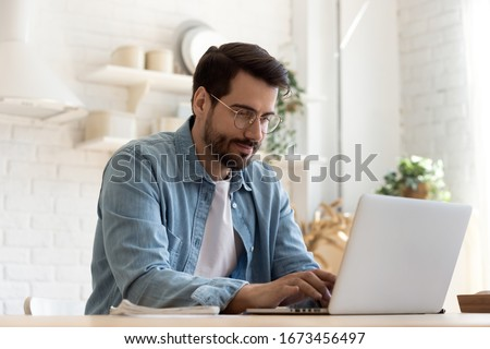 Focused young man wearing glasses using laptop, typing on keyboard, writing email or message, chatting, shopping, successful freelancer working online on computer, sitting in modern kitchen Royalty-Free Stock Photo #1673456497