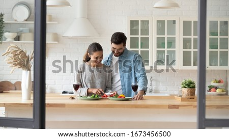 Happy young loving couple preparing dinner in kitchen at home together, celebrating anniversary, enjoying romantic date, drinking red wine, smiling beautiful wife cutting vegetables for salad #1673456500