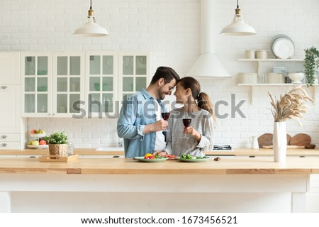 Happy loving couple holding wine glasses, touching foreheads, enjoying tender moment, romantic date, standing in modern kitchen at home together, smiling wife and husband celebrating anniversary #1673456521