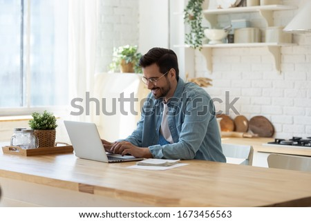 Smiling young man working on laptop in modern kitchen, checking email in morning, writing message in social network, happy young male using internet banking service, searching information Royalty-Free Stock Photo #1673456563