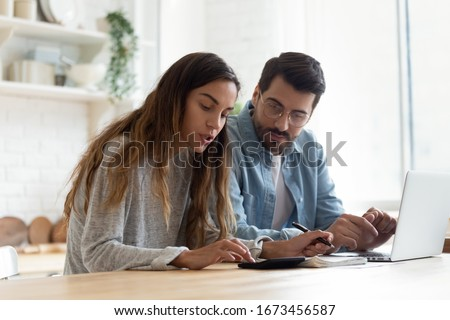 Serious wife and husband planning budget, checking finances, focused young woman using calculator, counting bills or taxes, man using laptop, online banking services, sitting at table in kitchen #1673456587