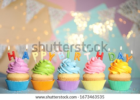 Birthday cupcakes with burning candles on grey table
