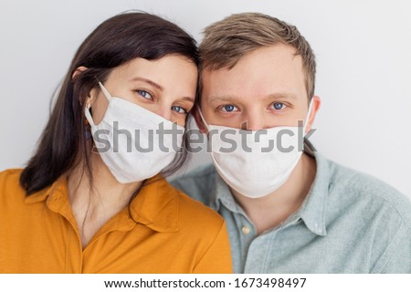 Faces of people in protective masks from coronavirus hand made. A beautiful blue-eyed quarantined couple protecting themselves from a pandemic. Positive young youth. Lifestyle COVID-19 home together #1673498497