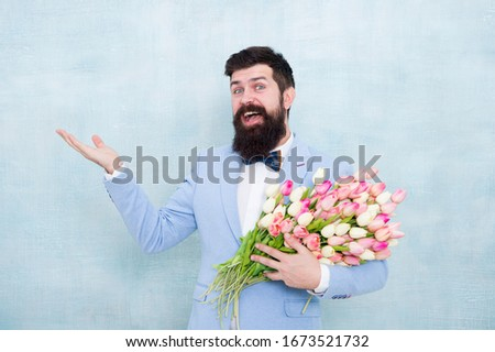 Shop now. Happy hipster with tulips. Bearded man with spring flowers. Flowering present. Floral present for Valentines day. Valentines or womens day present. Valentine man hold empty hand, copy space. #1673521732