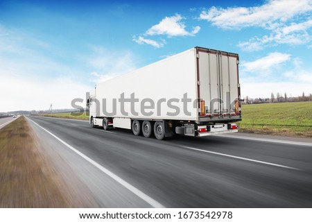 A big white truck and a trailer with space for text on the countryside road in motion against a blue sky with clouds #1673542978