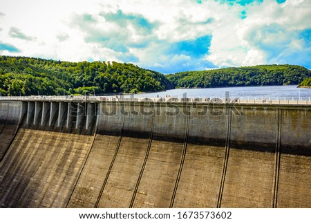 Sunny day view of the huge dam and the water behind it, surrounded by forests #1673573602