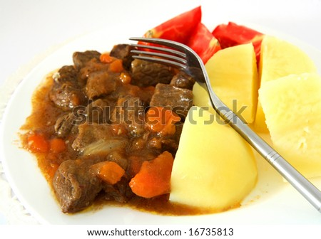 A beef stew with carrots and onion, boiled potatoes and tomato wedges. #16735813