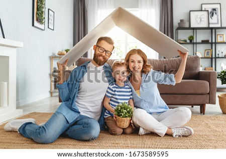 Cheerful parents with childr smiling and keeping roof mockup over heads while sitting on floor in cozy living room during relocation