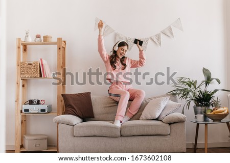 Charming girl in tracksuit dancing, sitting on couch. Woman holding smartphone and listening to music with headphones. Shot of teen in pink home suit having fun in cozy home atmosphere #1673602108