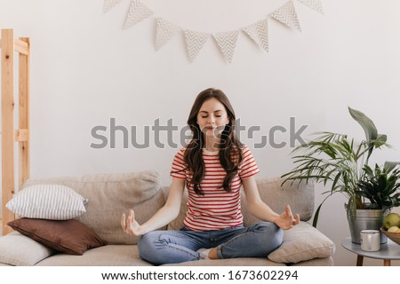 Brunette girl in striped T-shirt is meditating while sitting on sofa in living room. Calm woman in red tee relaxing on beige couch at home #1673602294