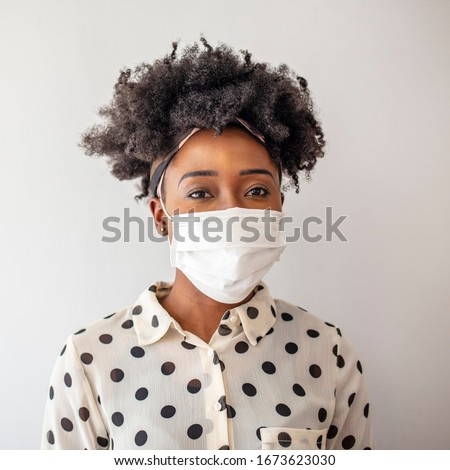 Studio portrait of young woman wearing a face mask, looking at camera, close up, isolated on gray background. Flu epidemic, dust allergy, protection against virus. City air pollution concept #1673623030
