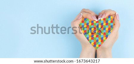 puzzle pattern heart in female hands on light blue background. World Autism Awareness day #1673643217