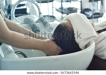 Hairdresser in beauty salon massage head customer and hair care in procedure of steaming water steam. Service steaming ozone in spa and salon shop. #1673662546