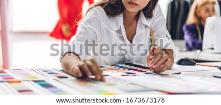 Portrait of young beautiful pretty woman fashion designer stylish sitting and working with color samples.Attractive young girl working with mannequins standing and colorful fabrics at fashion studio