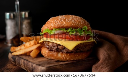 Close up view of Fresh tasty beef burger  and french fries on wooden tray with seasoning on rustic table #1673677534