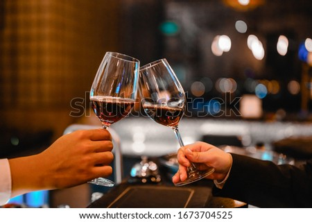 Two bartender enjoying of Cheers glass of wine for wine tasting event in a restaurant  at sunset. bartender, tasting, Dinner, Wine, beverage, dinner concept. #1673704525