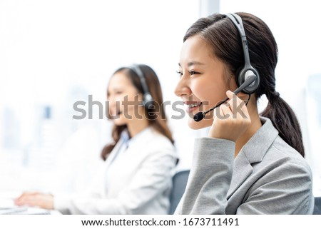 Smiling telemarketing Asian woman working in call center office Royalty-Free Stock Photo #1673711491