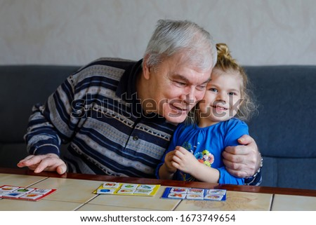 Beautiful toddler girl and grandfather playing together pictures lotto table cards game at home. Cute child and senior man having fun together. Happy family indoors