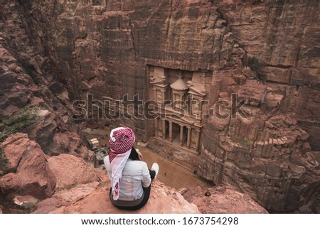 Tourist sitting in front of the Treasury in Petra ruin and ancient city in Jordan, Arab, Asia #1673754298