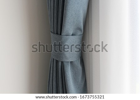 Light blue mix with grey curtain tie back or curtain straps tied the curtain with the white sheer background. Soft and smooth  mood with copy space. Curtains are in ling room. #1673755321