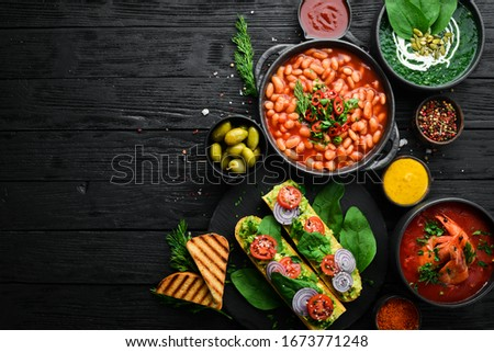 Set of food on black stone background. Dishes of beans, vegetables and seafood. #1673771248
