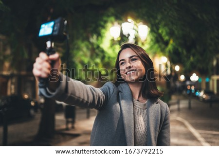 Female vlogger record with digital camera. Smiling woman taking selfie video on light night city. Traveler making video for her blog. Vlogger uses photo camera for shoot social media